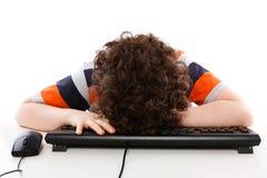 Kind, das auf comuputer Tastatur schläft Stockbild