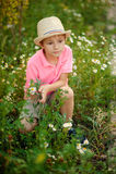 Kind, das auf das Gras mit Gänseblümchen legt Lizenzfreie Stockbilder