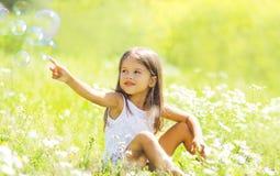 Kind, das auf dem Gras auf dem Sommergebiet sitzt Stockfotografie