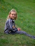Kind, das auf dem Gras sitzt stockbilder