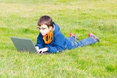 Kind, das auf dem Gras studiert Stockbilder