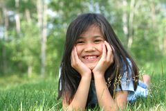Kind, das auf dem Graslächeln liegt Lizenzfreie Stockfotografie