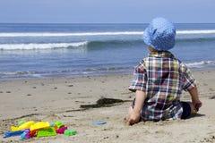 Kind, das auf dem Strand sitzt und das Wasser betrachtet Lizenzfreie Stockfotografie