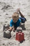 Kind, das auf dem Strand spielt. Lizenzfreies Stockbild