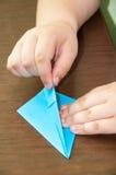 Kind, das auf dem Tisch Origamiflugzeug herstellt Lizenzfreie Stockfotografie