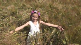 Kind, das auf dem Weizen-Gebiet, glückliches Jungen-Gesichts-lächelndes Porträt-Mädchen im Freien spielt stockbilder