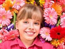 Kind, das auf den Blumen liegt. Lizenzfreie Stockbilder