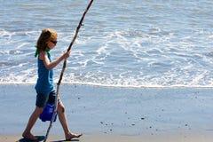 Kind, das auf den Strand mit einem Steuerknüppel geht Stockfotos