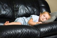 Kind, das auf der Couch liegt Lizenzfreie Stockfotografie