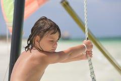 Kind, das auf der Yacht steht und versucht zu helfen, das Boot für die Reise vorzubereiten Stockbilder