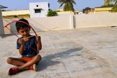 Kind, das auf die Dachoberseite sitzt und mit Pfeil und Bogen spielt lizenzfreies stockbild