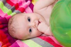 Kind, das auf einem bunten Tuch liegt Stockfotografie