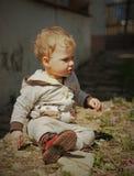 Kind, das auf einem Gartenweg sitzt Lizenzfreie Stockbilder
