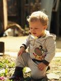 Kind, das auf einem Gartenweg sitzt Lizenzfreies Stockbild