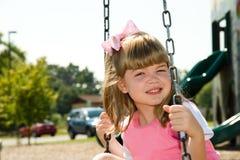 Kind, das auf einem Gummireifen-Schwingen am Park schwingt Stockbilder