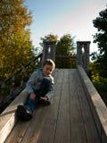 Kind, das auf einem hölzernen Hügel sitzt  Stockfotografie