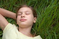 Kind, das auf einer grünen Wiese liegt Lizenzfreie Stockfotografie