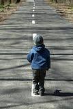 Kind, das auf einer Landschaftstraße steht lizenzfreie stockbilder