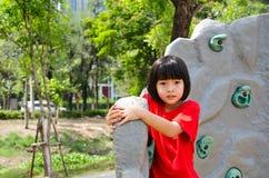 Kind, das auf einer Wand im Park steigt Lizenzfreie Stockbilder