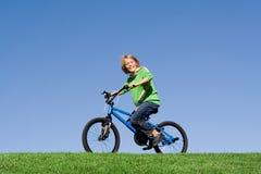 Kind, das auf Fahrrad spielt lizenzfreies stockfoto