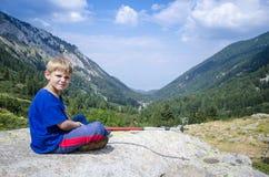 Kind, das auf Felsen in den Bergen sitzt Stockfotos