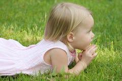 Kind, das auf Gras legt Stockfoto