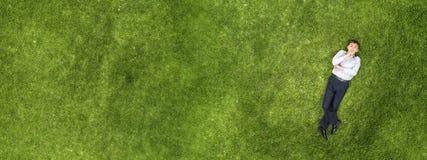 Kind, das auf Gras sich entspannt lizenzfreies stockbild