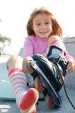 Kind, das auf ihren Rollerbladerochen sich setzt Stockbilder
