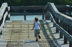 Kind, das auf Pier läuft Stockfotos