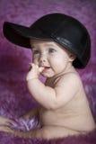 Kind, das auf purpurrotem Pelz sitzt Stockfotos