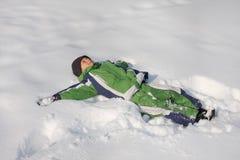 Kind, das auf Schnee legt Stockfoto