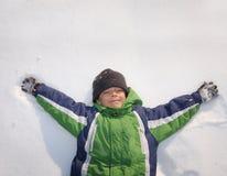Kind, das auf Schnee legt Lizenzfreie Stockbilder