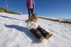 Kind, das auf Schnee nahe bei Mutter sitzt Lizenzfreie Stockfotografie