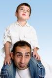 Kind, das auf Schultern des Vaters sitzt stockfotos