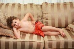 Kind, das auf Sofa legt Lizenzfreie Stockbilder