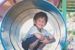 Kind, das auf Spielplatz spielt Lizenzfreie Stockfotos