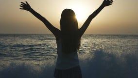 Kind, das auf Strand, Kind betrachtet Wellen Sonnenuntergang, Mädchen-Schattenbild auf Küste spielt stockfotografie