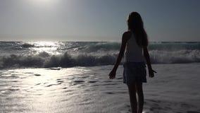 Kind, das auf Strand im Sonnenuntergang, Kinderaufpassende Meereswellen, Mädchen-Porträt auf Ufer spielt stock footage