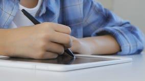 Kind, das auf Tablet, Mädchen schreibt in die Schulklasse, lernend studiert, Hausarbeit tuend lizenzfreies stockfoto