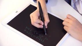 Kind, das auf Tablet, M?dchen schreibt in die Schulklasse, lernend studiert, Hausarbeit tuend stock footage