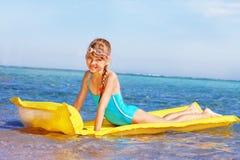 Kind, das aufblasbare Strandmatratze schwimmt. Lizenzfreie Stockfotografie