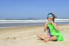 Kind, das aufblasbaren Schwimmenring auf dem Strand aufbläst Stockfotos
