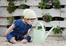 Kind, das aus den Grund in Gartenarbeitausstattung mit Blume im Hintergrund sitzt Stockbilder