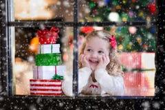 Kind, das aus Fenster auf Weihnachtsabend heraus aufpasst Lizenzfreie Stockbilder