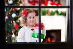 Kind, das aus Fenster auf Weihnachtsabend heraus aufpasst Lizenzfreie Stockfotos