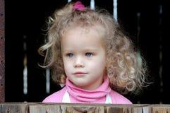 Kind, das aus Fenster heraus schaut Stockfotos