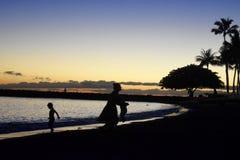 Kind, das bei Sonnenuntergang mit seiner Familie spielt Lizenzfreies Stockbild