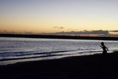 Kind, das bei Sonnenuntergang spielt Stockfoto