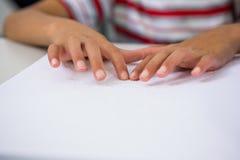 Kind, das Blindenschrift-Buch im Klassenzimmer liest Lizenzfreie Stockfotos