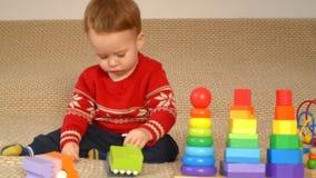 Kind, das bunte Spielwaren spielt stock footage